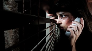 Fearful battered woman peeking through the blinds calling for help phot