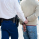 An assaulted Law Enforcement officer leads away the accused, handcuffed
